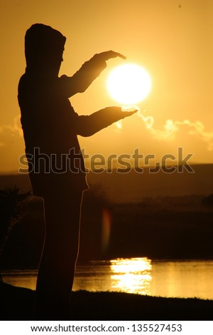 silhouette of a person holding the sun
