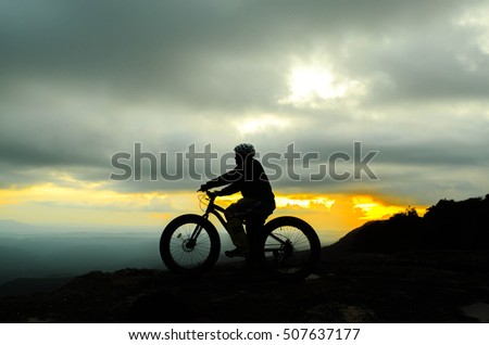 silhouette of a rider on hill with cloudy