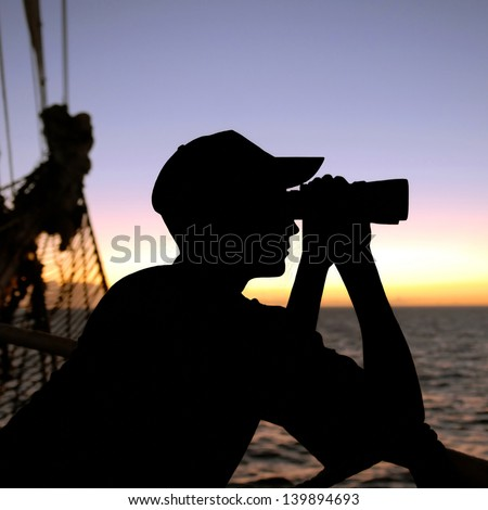 silhouette of a ship captain looking through binoculars