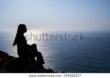 Silhouette of a woman sitting on top of a cape with the sea or ocean in background. Concept for sadness, loneliness, contemplation or relaxation emotions.
