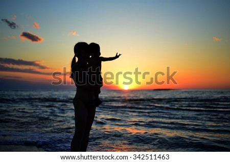 Silhouette of a woman with a baby on a background of dawn