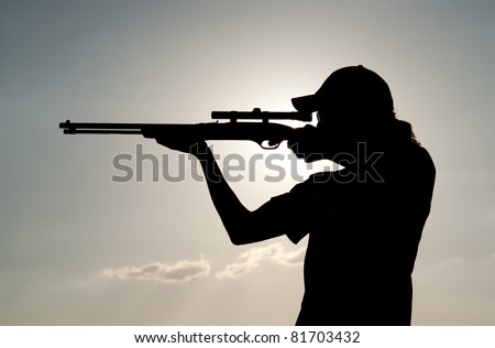 Silhouette of a young man with ponytail shooting against sunset