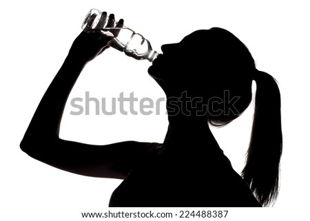silhouette of a young woman drinks water from a bottle