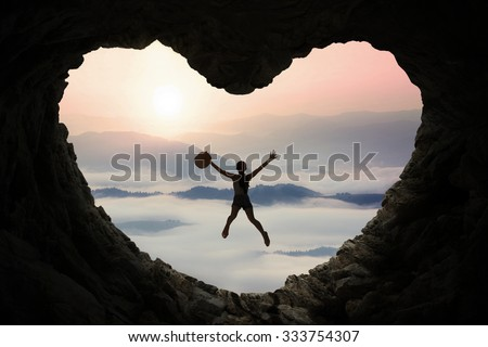 Silhouette of attractive woman jumping inside cave shaped heart symbol and holding hat