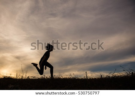 Silhouette of Beautiful Woman practicing yoga on lawn at sunset