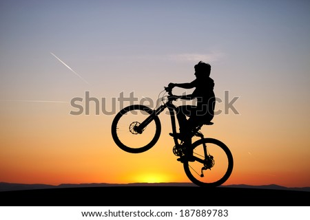 silhouette of boy riding his mountainbike in sunset