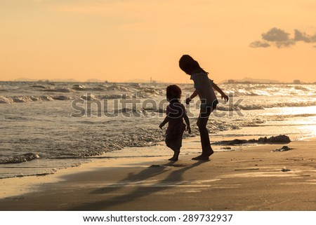 Silhouette of Brother and Sister Play on the Beach