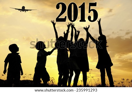 Silhouette of children running and jumping on the summer sunset meadow for happy new 2015 year