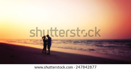 silhouette of couples hugging on the beach on the beach with sunrise in the sea for valentine's day, blurred
