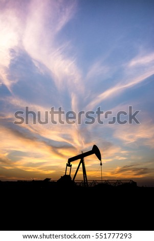 Silhouette of crude oil pump at sunset blue hour in the oilfield