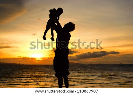 silhouette of daddy and small girl on the beach at dusk.