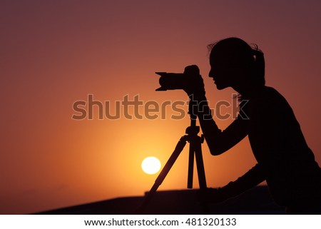 Silhouette of female photographer taking pictures during sunset.