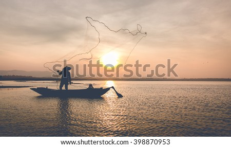 Silhouette of fishermen on wooden boat,he casting  for catching fish at lake in sunrise time,thailand (The casting people living along the River)