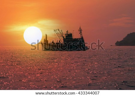 Silhouette of fishing boat  in the sea with colorful sunset background.