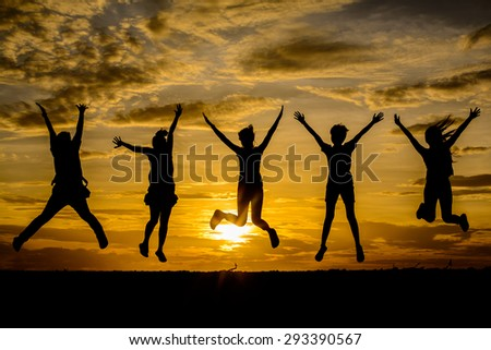 silhouette of friends jumping on beach during sunrise time