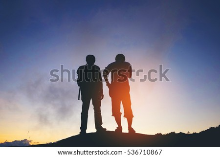 silhouette of friends standing in sunset