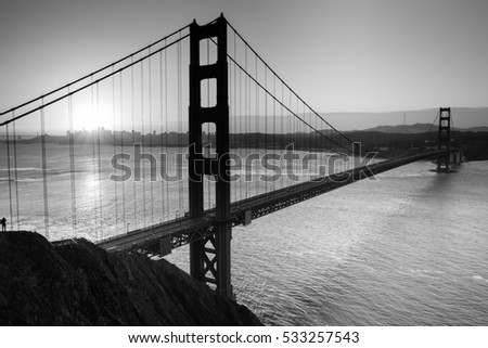 Silhouette of Golden Gate Bridge and a Photographer during Sunrise in Black and White