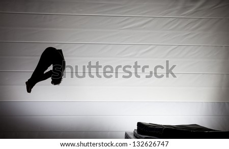 silhouette of gymnast in pike position on trampoline