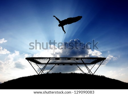silhouette of gymnast on trampoline in sunset