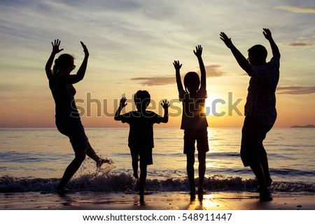Silhouette of happy family who playing on the beach at the sunset time. People having fun on the beach. Concept of friendly family and of summer vacation.