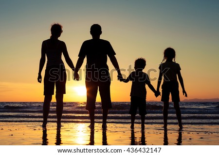 Silhouette of happy family who standing on the beach at the sunset time. Concept of friendship forever.