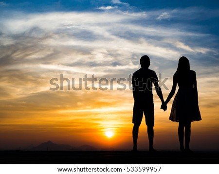 Silhouette of Happy Young Couple Hugging Outside at Sunset, Holding Hands and Talking