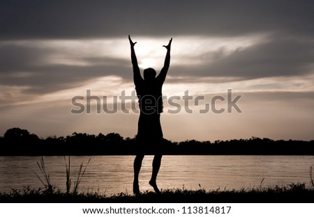 Silhouette of man on the river, holding his hands up, hugging the sun