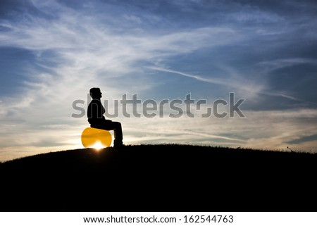 silhouette of man sitting on fitness ball in sunset sky