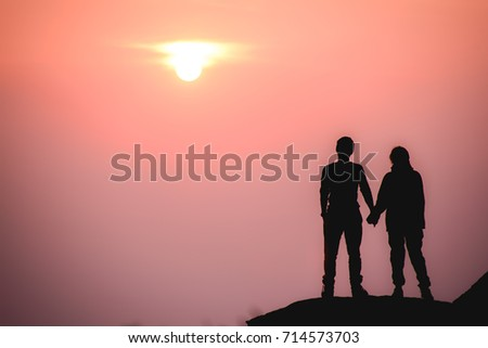 silhouette of romantic couple standing holding hands and watching beautiful sunrise in morning romance