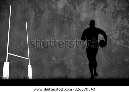 Silhouette of rugby player against black