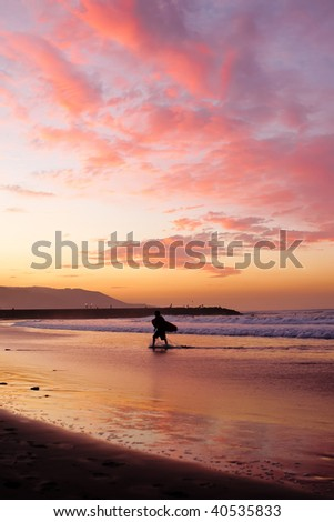 silhouette of surfer walking on sand at sunset