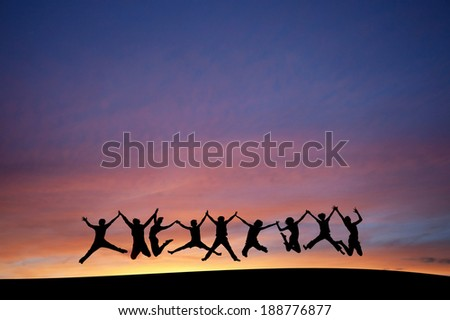 silhouette of teenagers jumping in sunset for fun