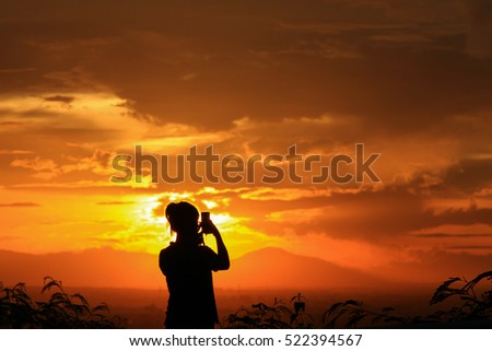 Silhouette of the woman standing at the view point during beautiful sunset.