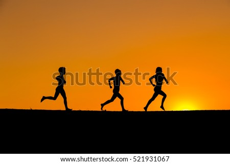 silhouette of three kids running against sunset