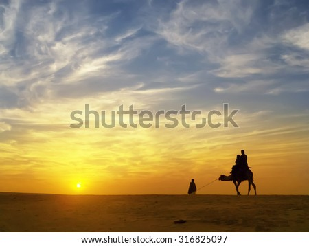 silhouette of tourist ride a camel who bought safari tour to see sunset at sand dune ,Thar desert,Jaisalmer,India