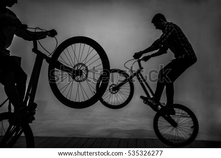 silhouette of  Two Young men performs stunts in photo studio isolated on white and gray background.  couple of gays male jump into the air with a bicycle