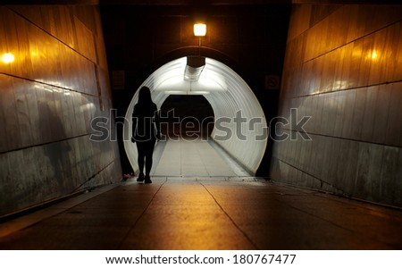 silhouette of Undefined woman walking into the Underground walkway