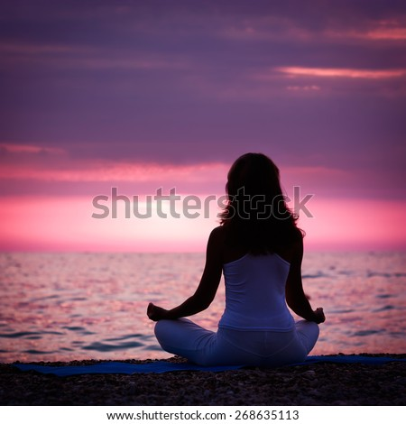Silhouette of Woman Meditating in Lotus Position by the Sea at Sunset. Rear View. Nature Meditaion Concept. Toned Instagram Styled Photo.