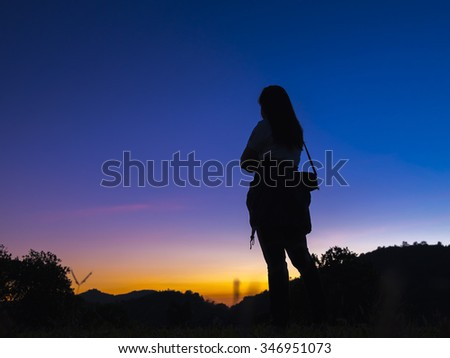 Silhouette of woman standing on top of mountains overlooking the forest at sunrise.
