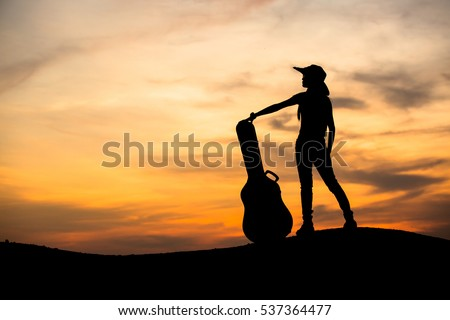 Silhouette of woman with guitar on the sunset