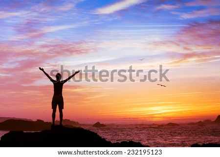 silhouette of woman with raised hands on beautiful sunset background
