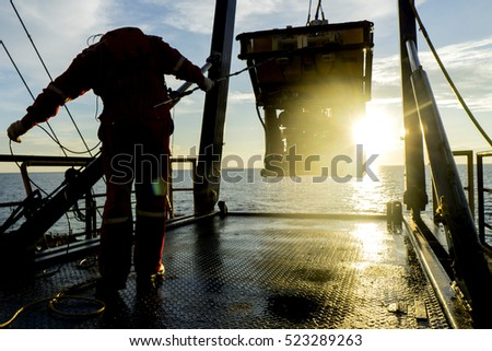 Silhouette of worker recovering robotics Remote Operated Vehicle (ROV) after entering sea surface during oil and gas pipeline inspection in the middle of South China Sea isolated on sunrise with glare
