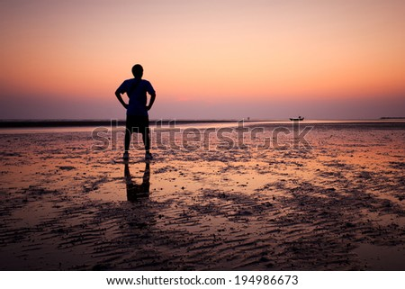 Silhouette of young man on the beach at sunset