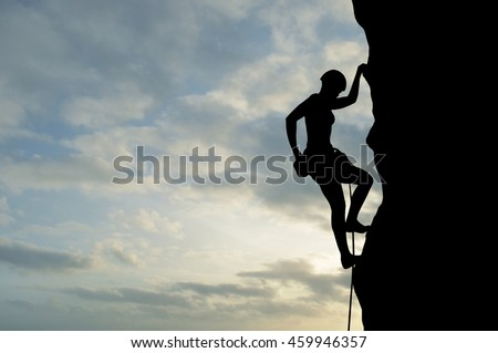 Silhouette of young woman lead climbing, sun, colorful sky and clouds behind. Climber on top rope, hanging on rock and putting hand to chalk bag with powder magnesium.