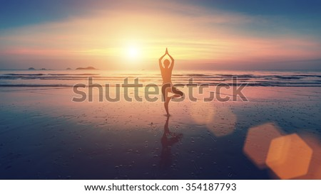 Silhouette of young woman practicing yoga on the beach at beautiful sunset.