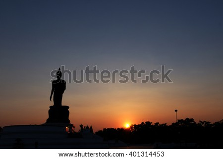 Silhouette public big white Buddha, over golden light sunset in Thailand background. Thailand travel concept. End of Buddhist Lent Day concept.