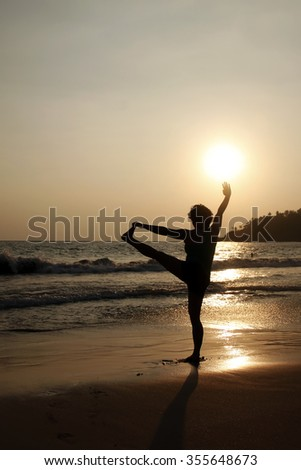 Silhouette yoga posture on the beach at sunset