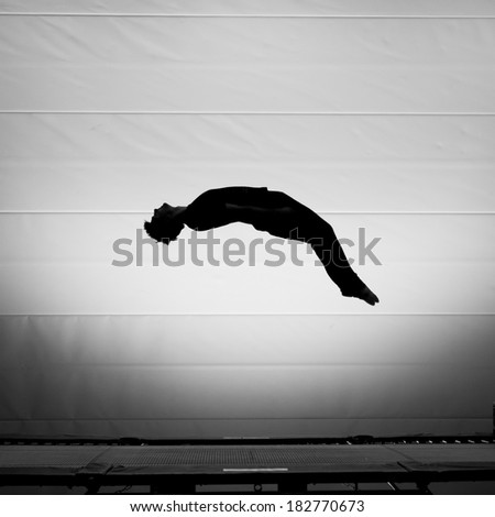 silhouetted man on trampoline