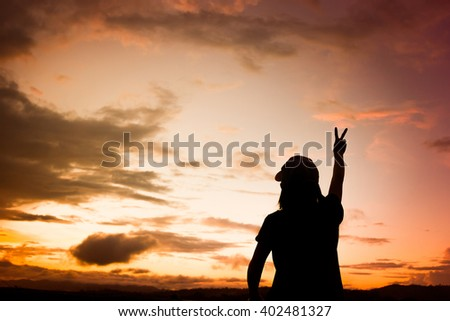 Silhouettes Asian Women over beautiful sun set background.
