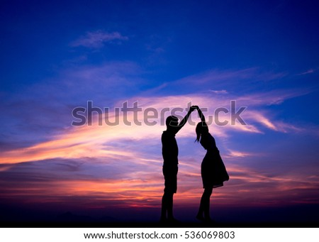 Silhouettes of couple gracefully dances in sunset